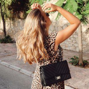 mujer rubia con bolso bandolera acolchado negro